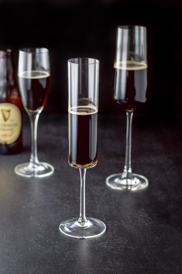 Guinness poured in the three champagne glasses with the bottle in the background