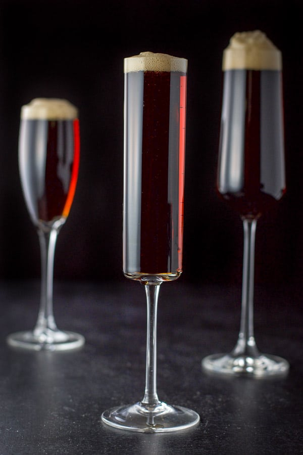 Vertical view of the three glasses of filled with the cocktail. Each with a big head on them
