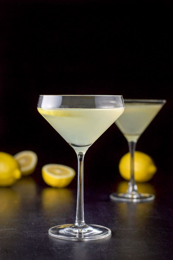 Curved martini glass in vertical view with the cocktail in it with lemons on the table