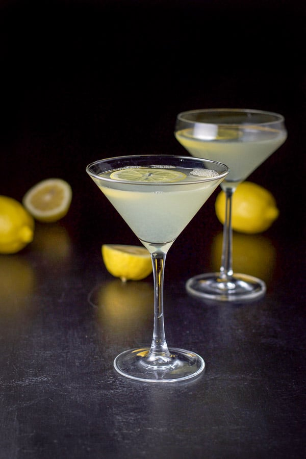 A classic martini glass filled with the lemon drink with the curved martini glass and lemons in the background