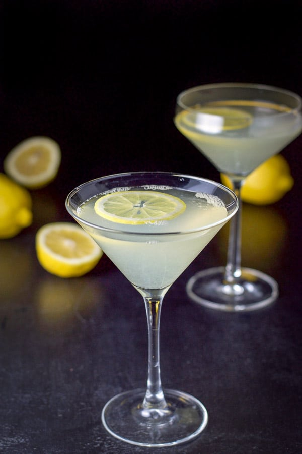 Lemon wheels floating in two martini glasses filled with the lemon cocktail