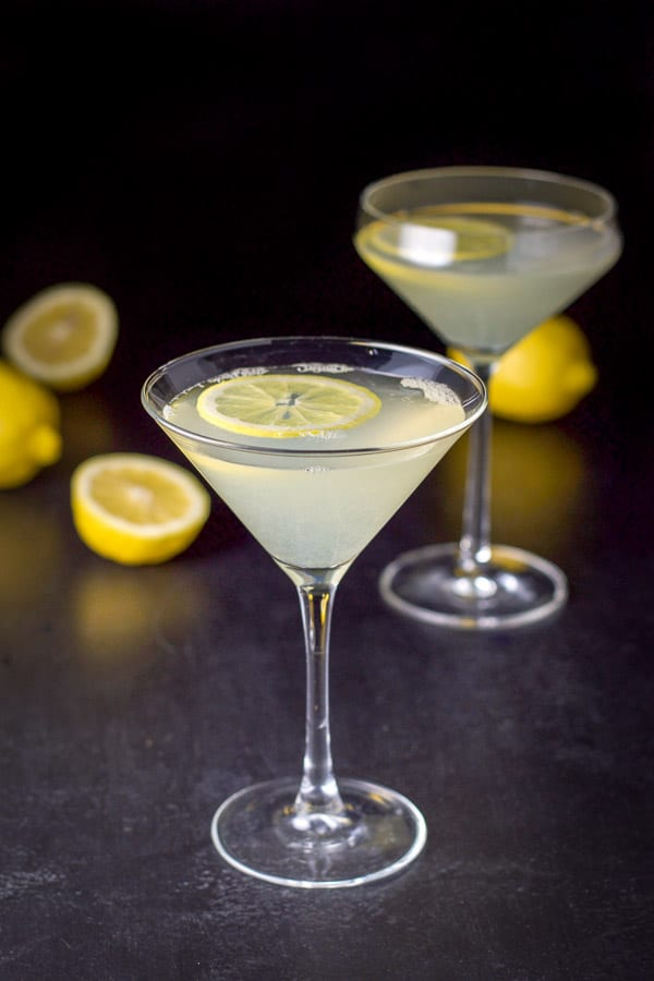 The classic glass in front of the curved martini glass with lemons floating in the cocktail and on the table