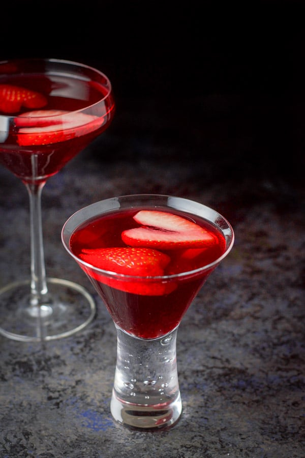 Short glass filled with the martini in front of the other one. There is strawberries floating in the drink