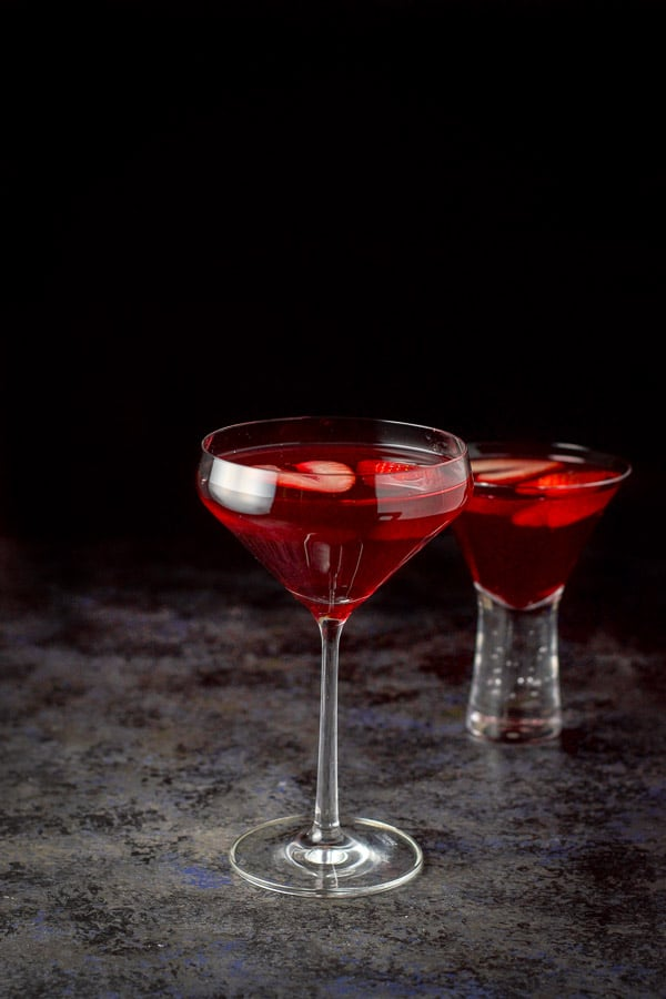 The red martini in a tall glass and a shorter glass behind it