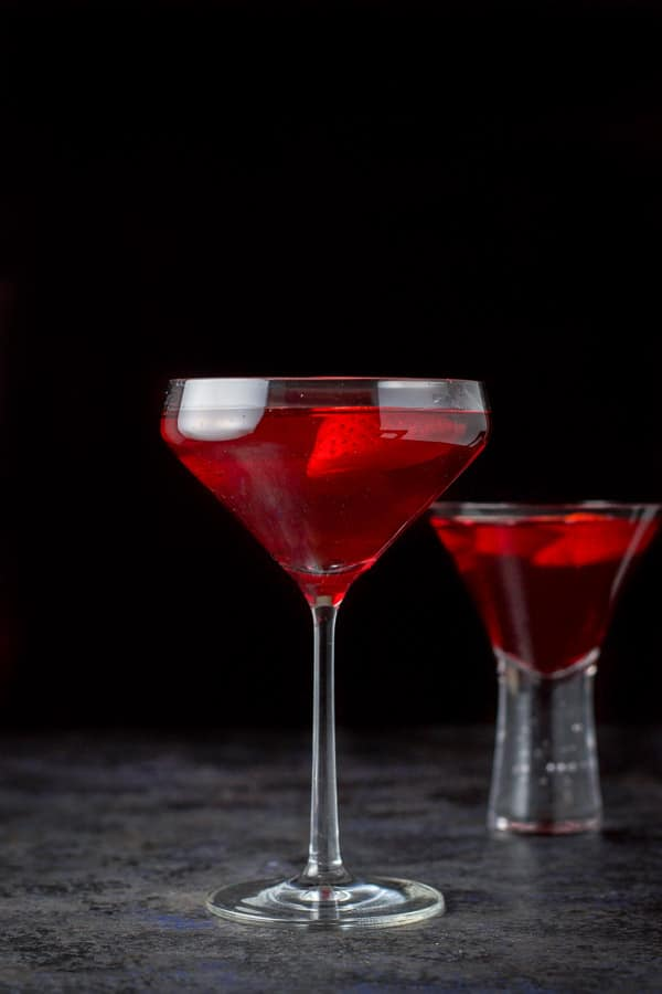 The red martini poured into two martini glasses - the taller glass in front and the bubble glass in back