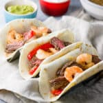 Square photo of 3 flour tortillas filled with shrimp and steak fajitas