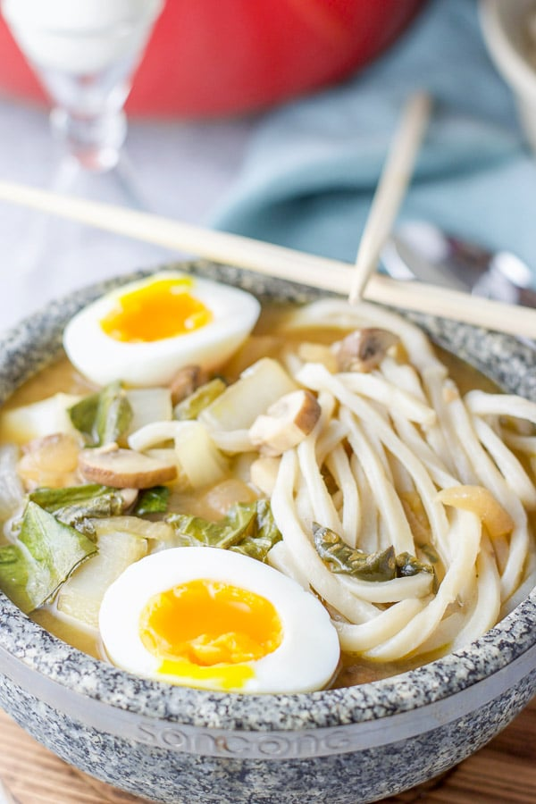 Close up of the noodle soup with the soft boiled egg in the stone bowl. There are chop sticks on the bowl