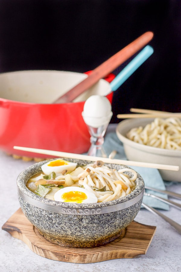 Further view of the Udon soup in a stone bowl with the pot in the background along with an egg and bowl of noodles
