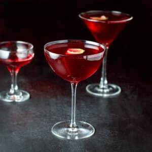 Three glasses filled with a red cocktail - square