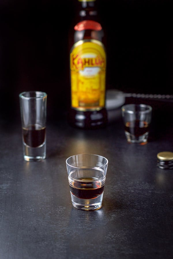 Kahlua poured out in the three shot glasses with the bottle in the background