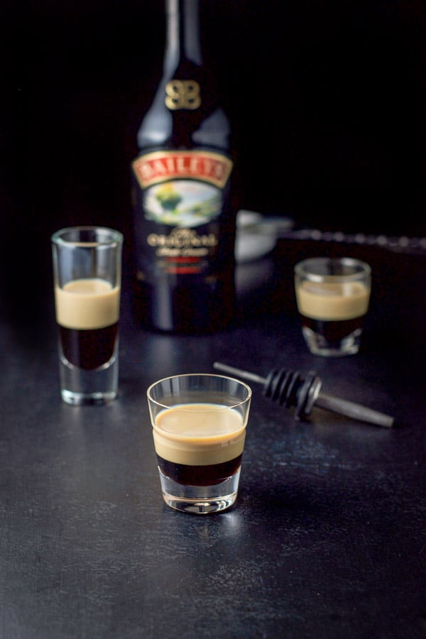 Baileys Irish cream layered on top of the Kahlua with the bottle in the background along with a pourer and cocktail spoon