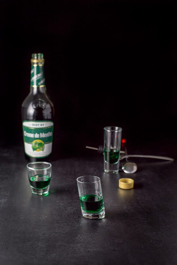 Green creme de menthe poured into the shot glasses with the bottle in the background