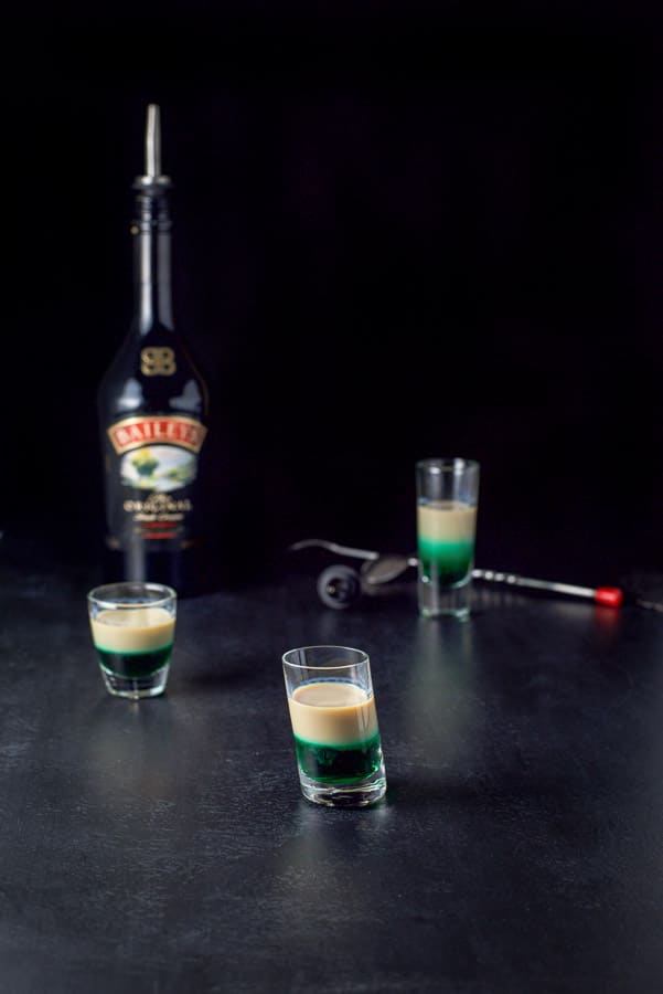 Baileys Irish cream layered into the three glasses with the spoon and bottle in the background