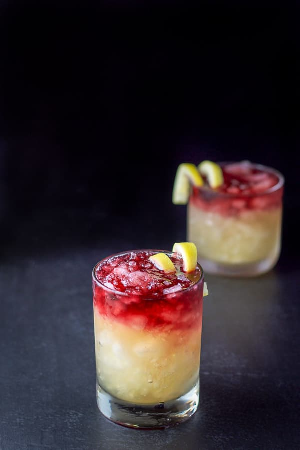 A higher view of the two glasses with the cocktails with lemon twist garnishes in them