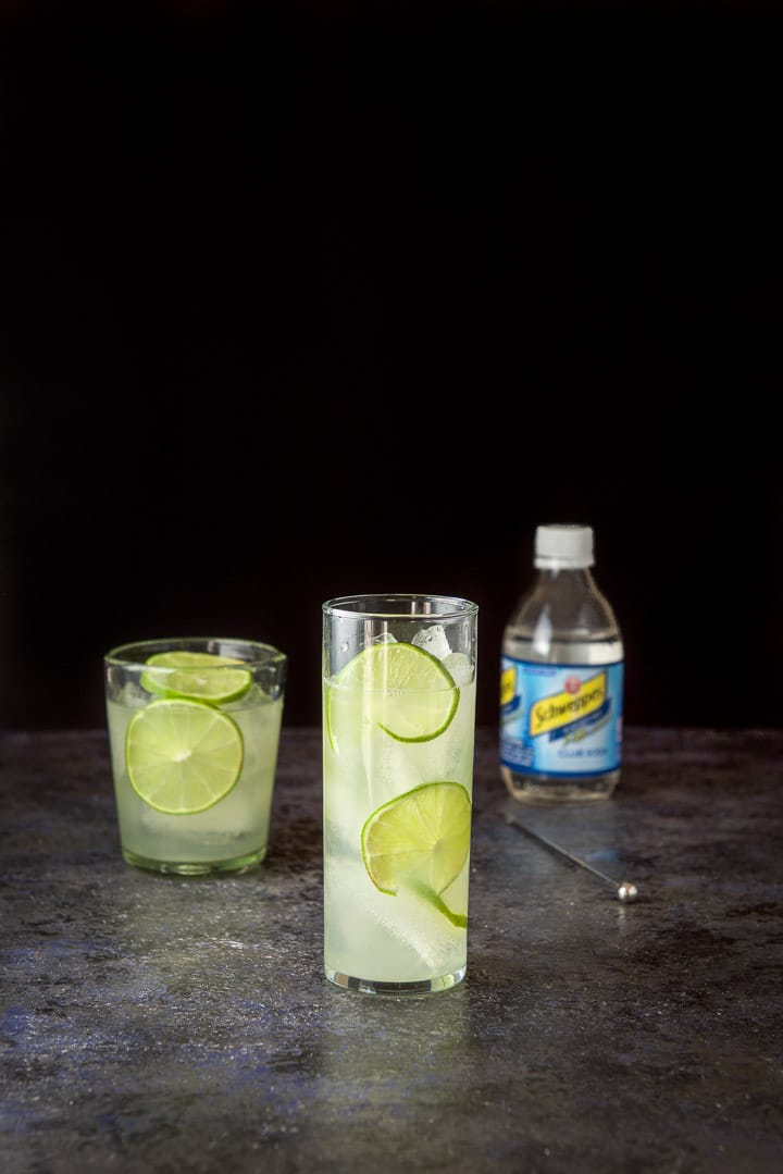 The gin and lime mixed into a glass with limes as garnish in the drink and club soda in the background