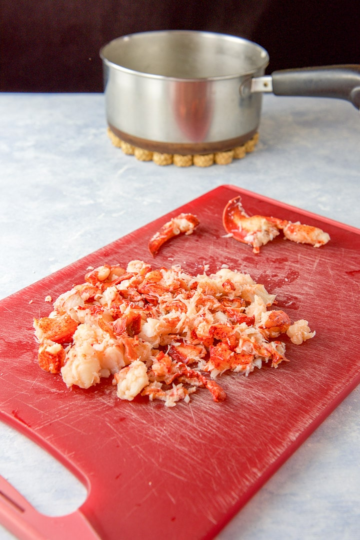 Lobster cut up on a red cutting board with a pan in the background