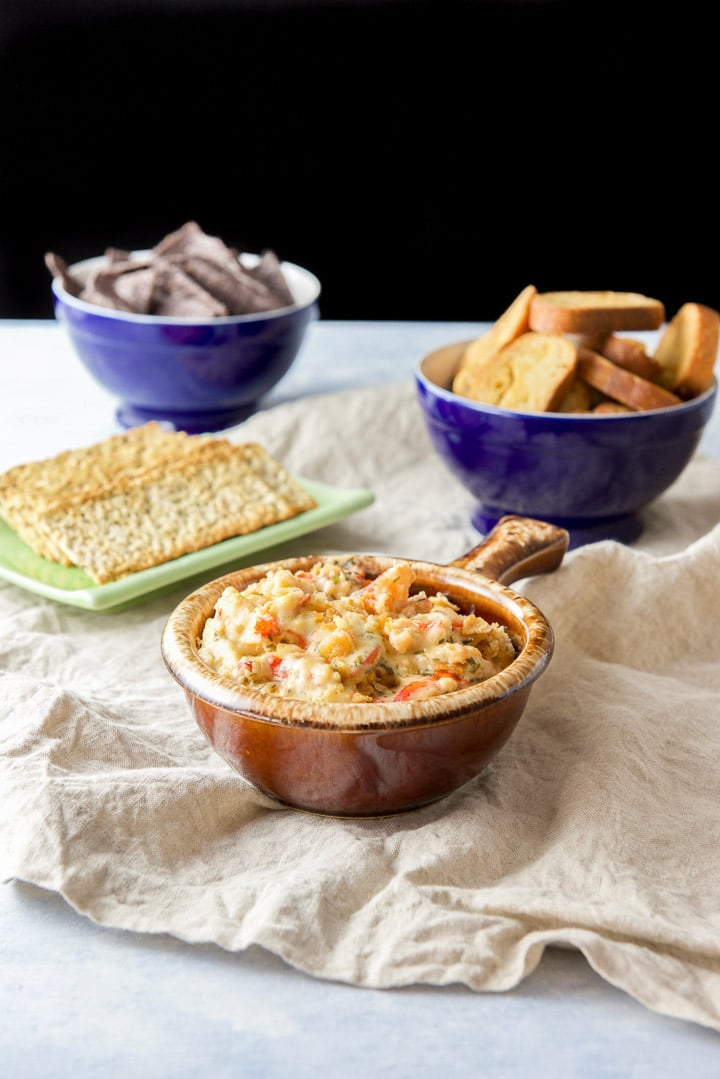 A brown crock filled with a chunky lobster dip with crackers, bread crisps and chips in the background