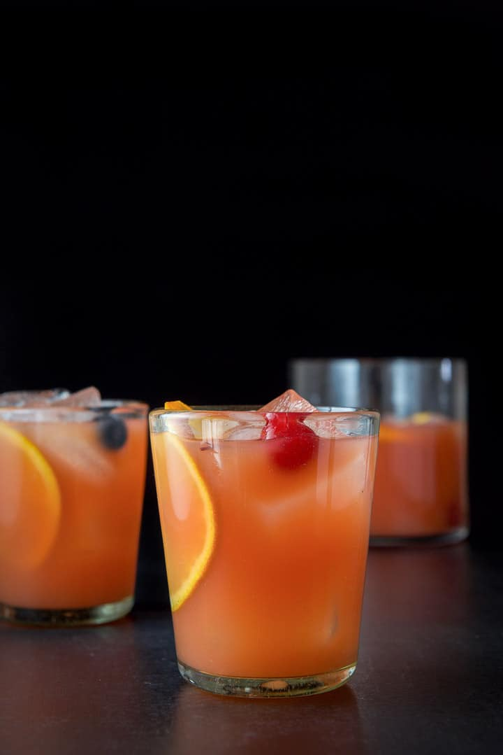Vertical view of the glasses filled with the scorpion bowl with cherries and oranges clearly showing