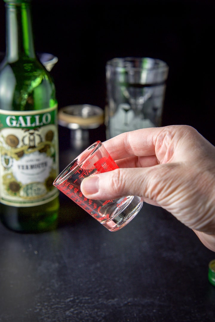 A female hand holding a shot glass with a small amount of vermouth with the bottle in the background