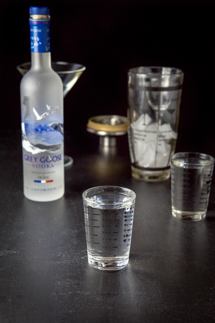 Vodka measured out with the Grey Goose bottle in the background along with an ice filled shaker