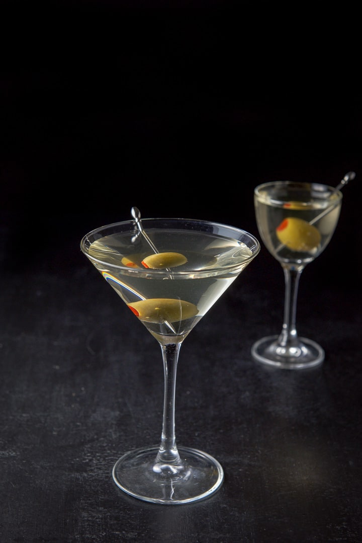 Two martini glasses filled with the martini with olives on picks as garnish