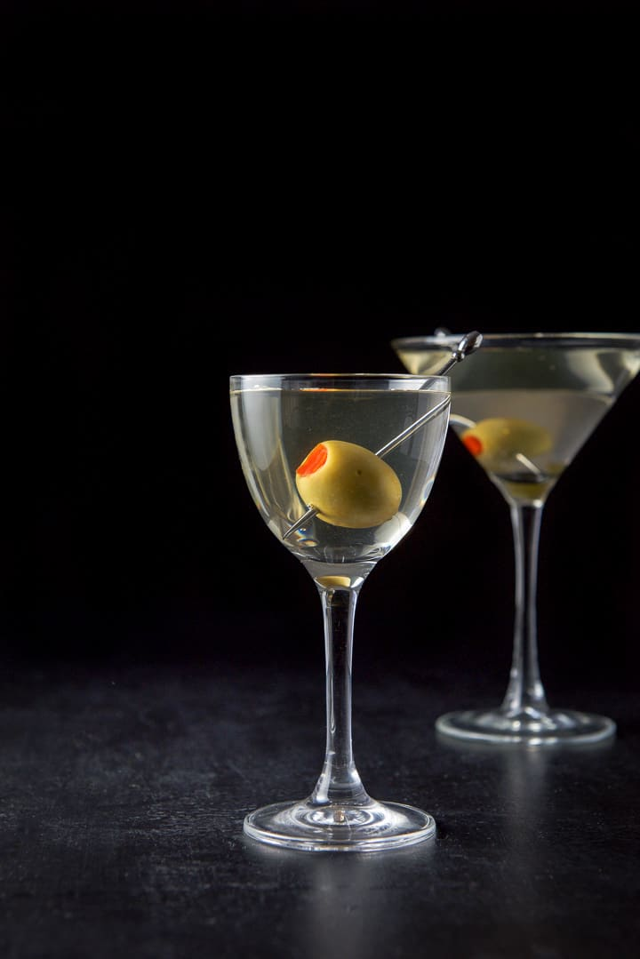 Vertical view of the smaller glass with the martini with a big olive in it. Regular martini glass in the background