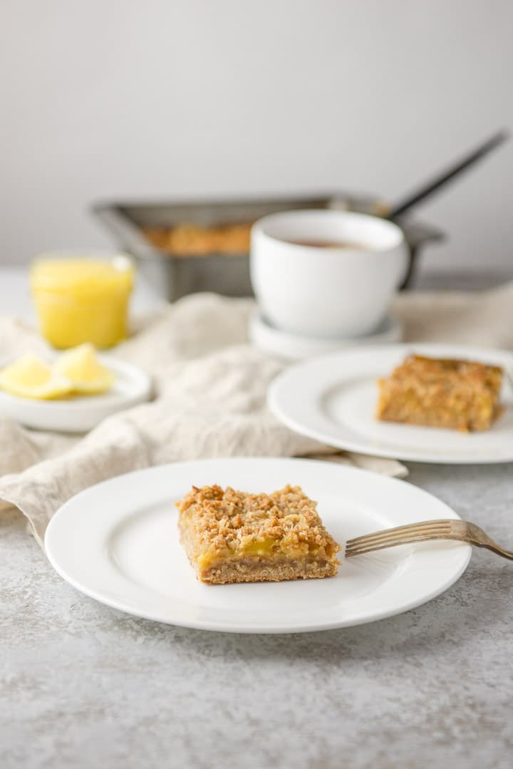 Lemon bars on two white plates with tea and the pan of bars in the background