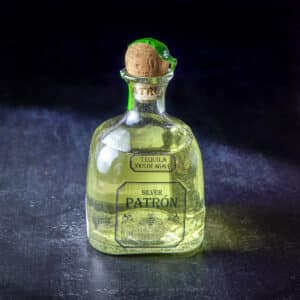 A bottle of infused tequila all green from the jalapeño - square