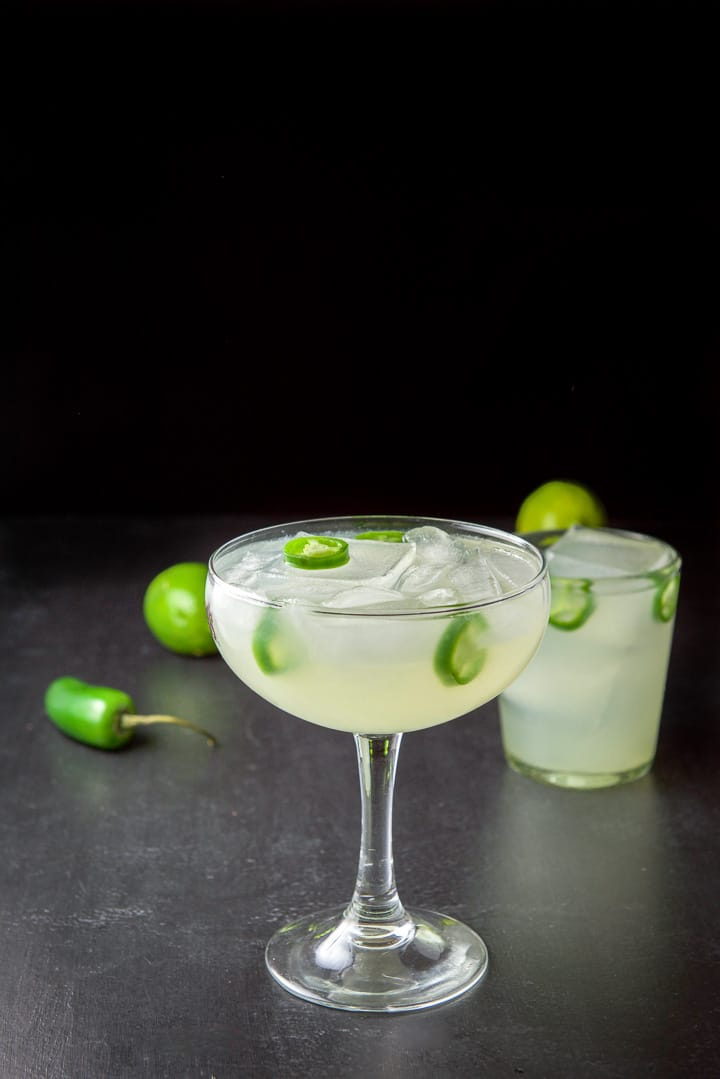 The margarita in the big bowl glass in front of the shorter glass. They both have jalapenos floating in the glasses