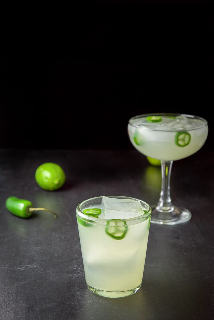 The short glass filled with the margarita in front of the taller glass