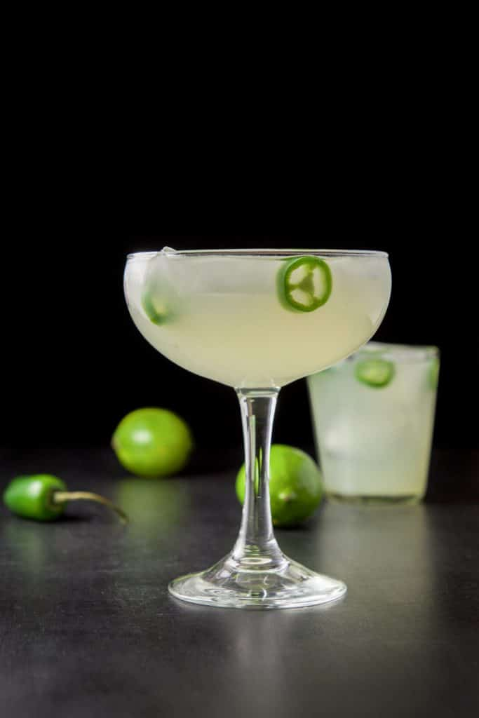Vertical view of the margarita with jalapeños floating in it and limes in the background