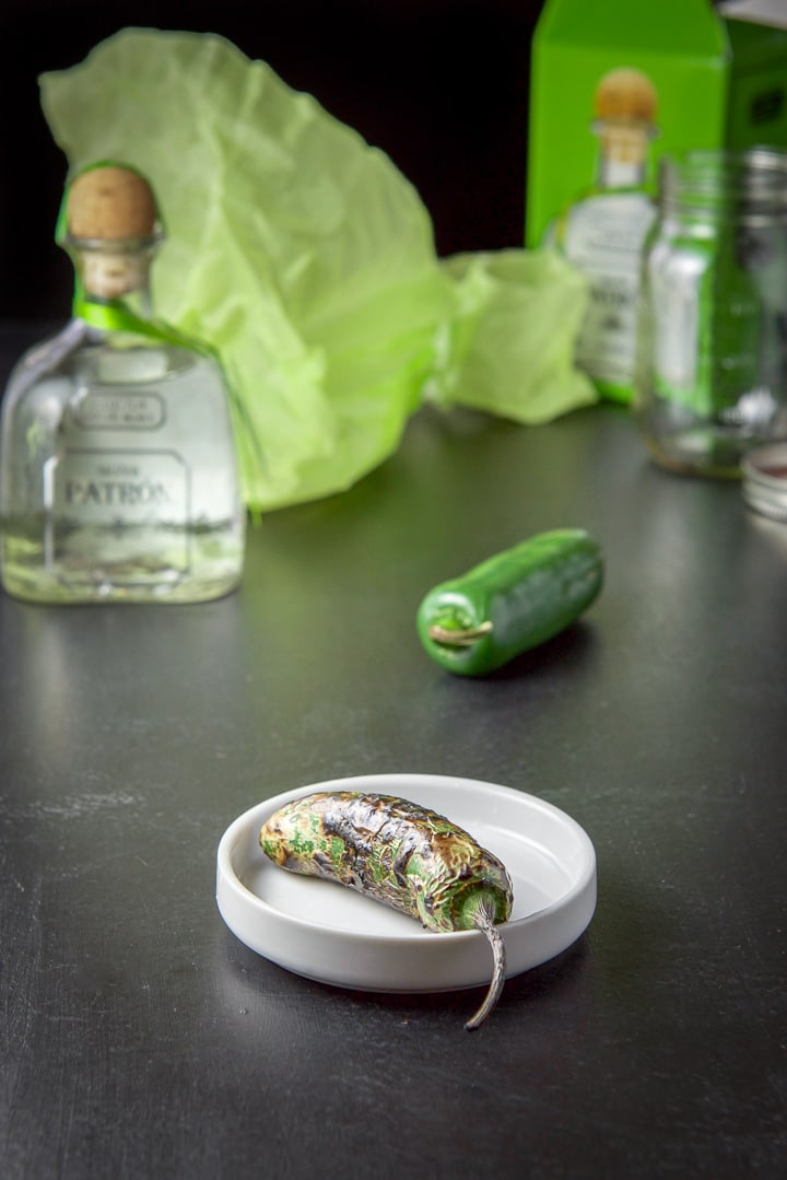 A roasted jalapeño in front and tequila and the box in the background
