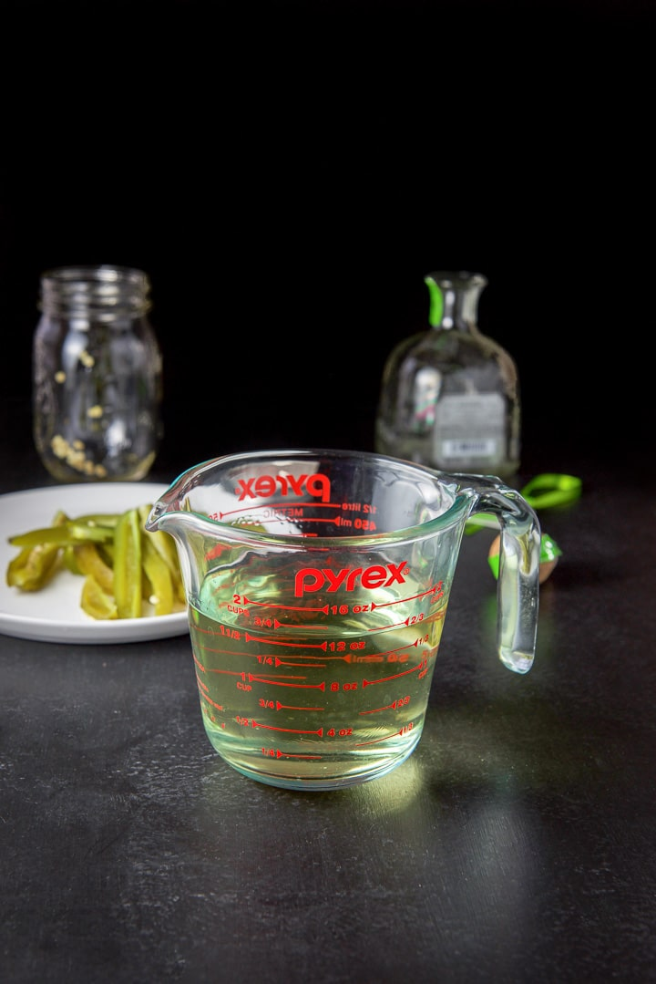 Strained infused tequila in a glass measuring cup with the jalapenos in the background