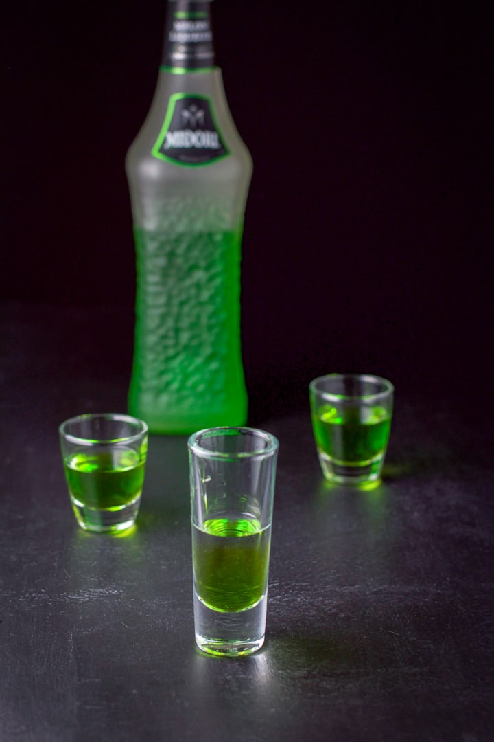 Midori layered in the three glasses with the bottle in the background