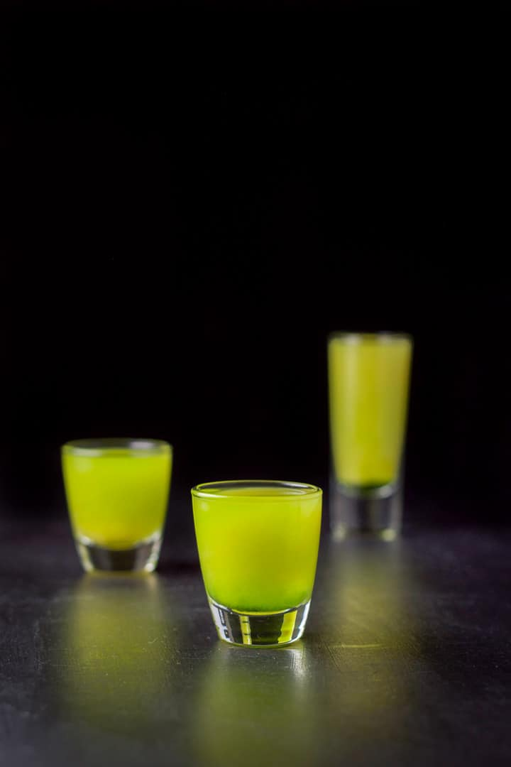 Short glass of the shot in front of the other two. You can see the Midori on the bottom with the juice at the top