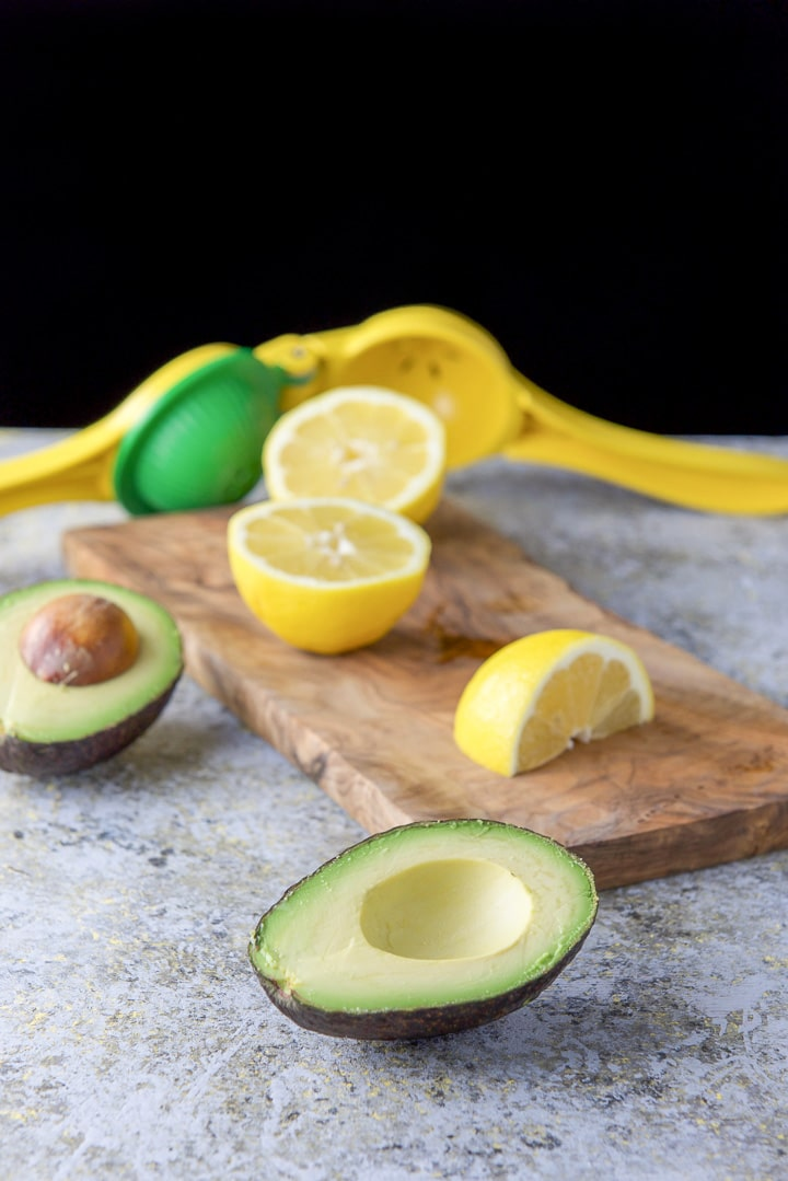 Avocado and lemons cut on a wooden board along with a citrus squeezer on the table