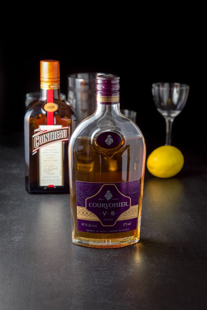 Courvoisier cognac, Cointreau, a lemon, two empty glasses and a cocktail shaker on a table