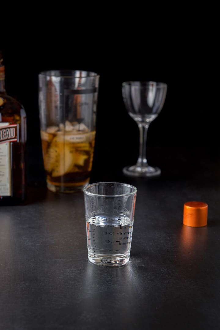 Cointreau measured out with the bottle, filled shaker and glass in the background