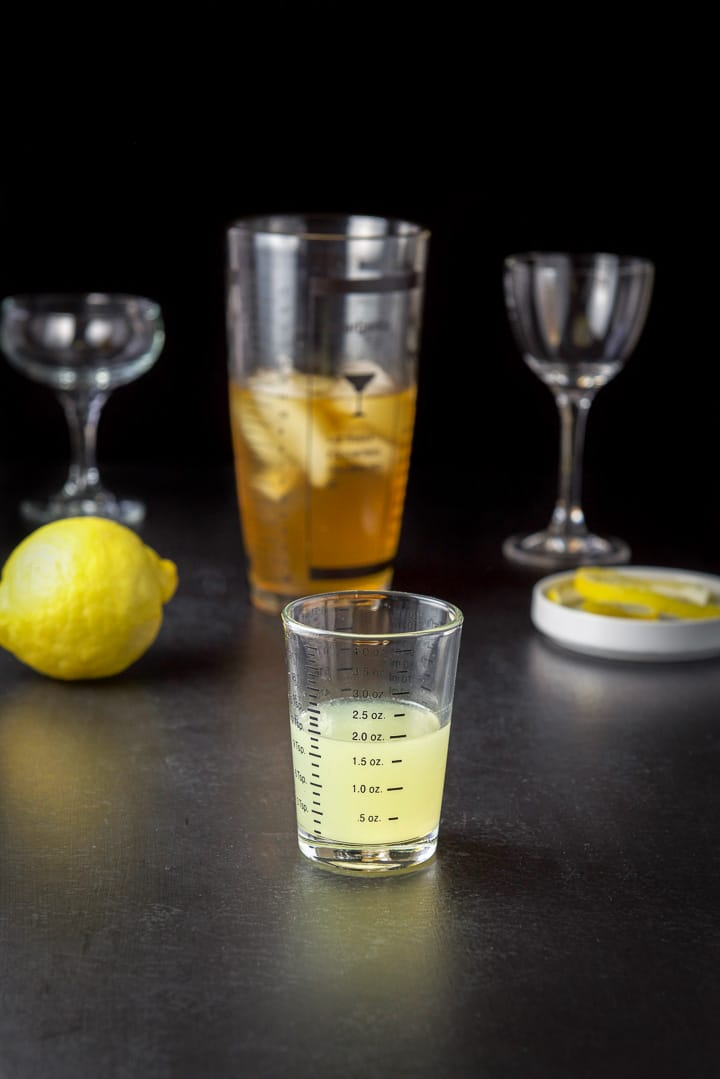 Lemon juice measured out with lemon, a cocktail shaker, lemon twists and glasses in the background