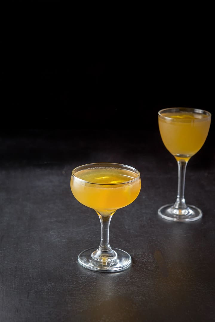 The amber cocktail in two glasses with lime twists