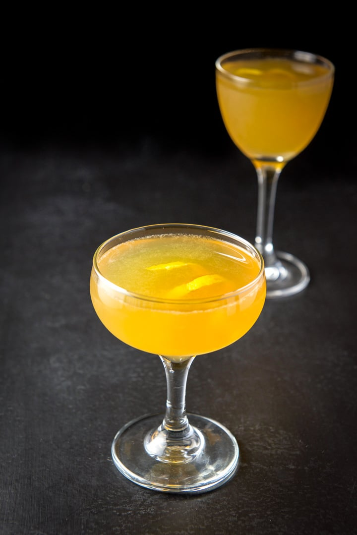 Close up of the golden yellow cocktail in the coupe glass with a lemon twist garnish and another cocktail in the background.