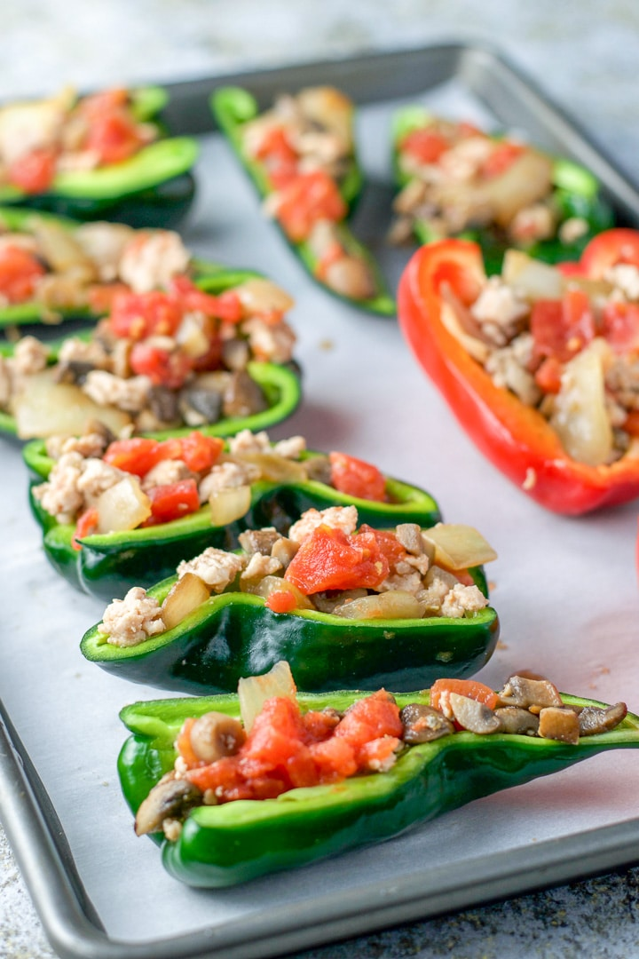 A pan full of peppers stuffed with chicken and veggies for the baked stuffed peppers