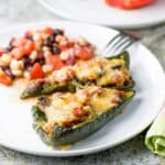 A white plate with two stuffed peppers and some bean salad - square