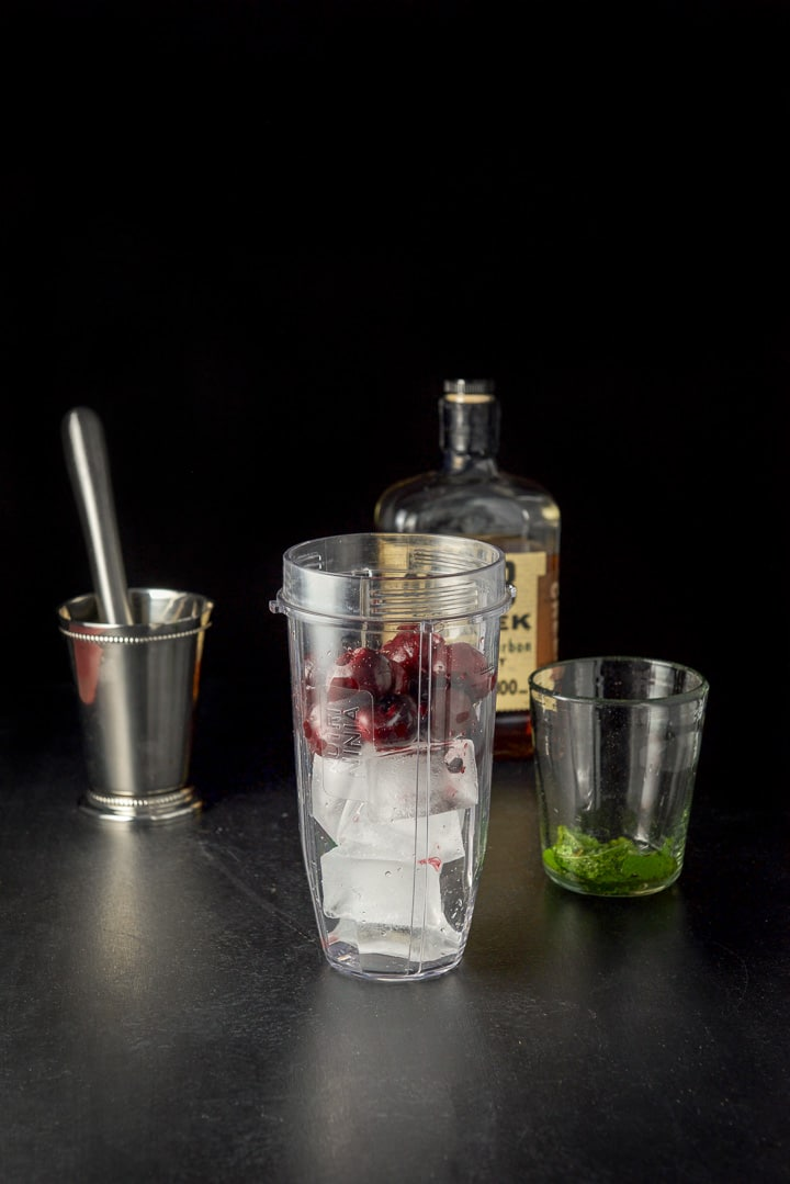 Ice cubes and pitted cherries in a blender container along with the metal cup, glass and bourbon in the background