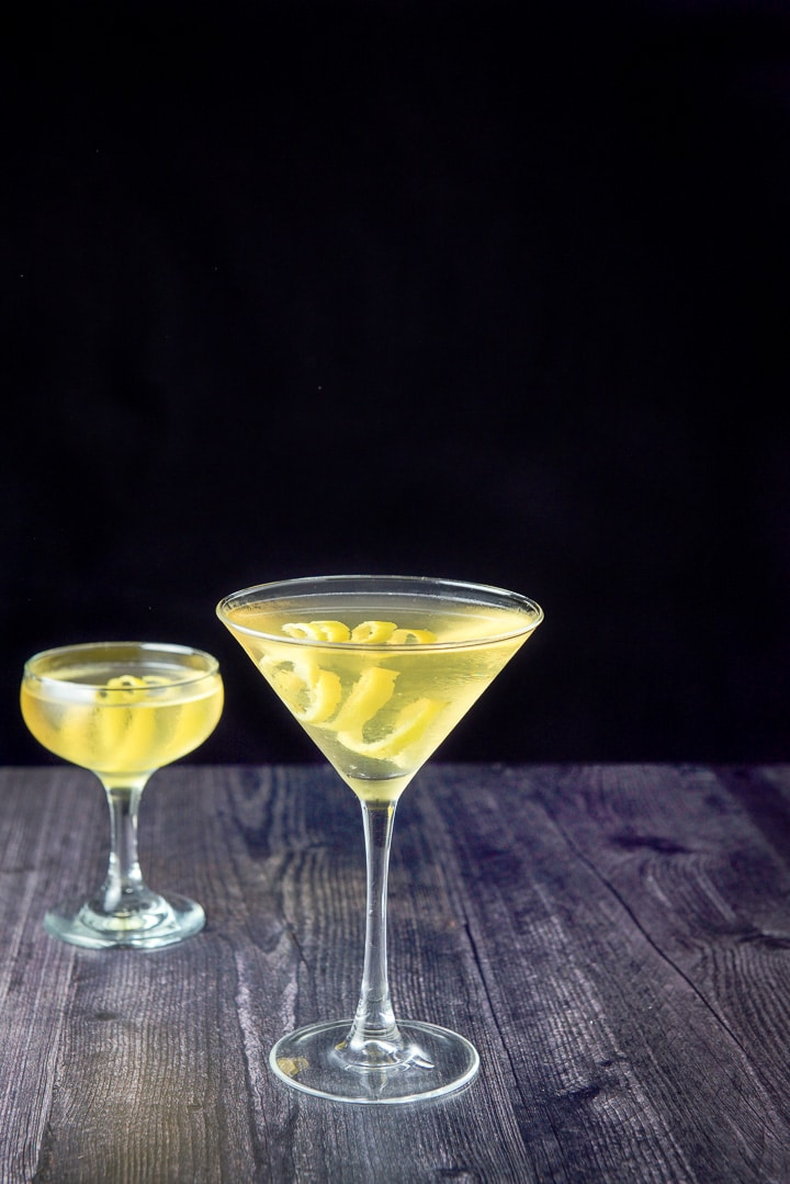 Classic martini glass in front of a coupe glass, filled with the Claridge. They both have lemon twists as garnish