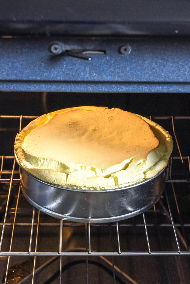 Baked cheesecake in the spring form pan, still in the oven with the door open.