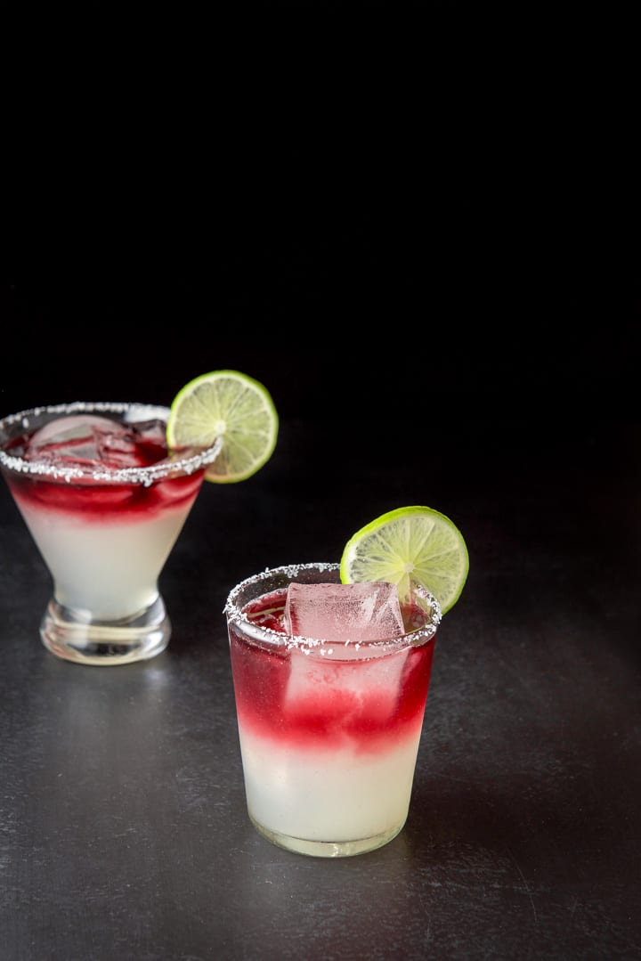 Two glasses with wine poured into the margarita. The lime wheels are on the rim