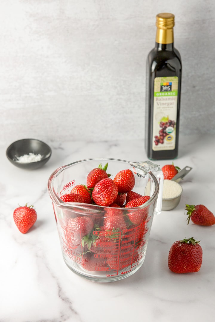 Strawberries in a measuring glass, sugar, corn starch and balsamic vinegar on a table