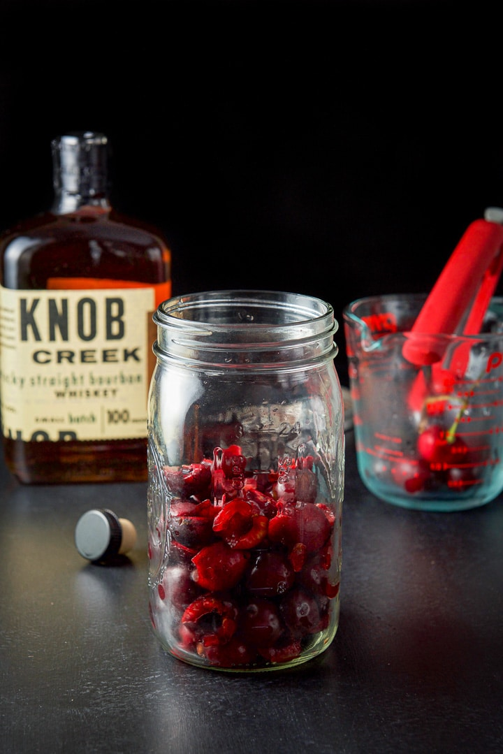 Pitted and halved cherries in a jar for the cherry bourbon