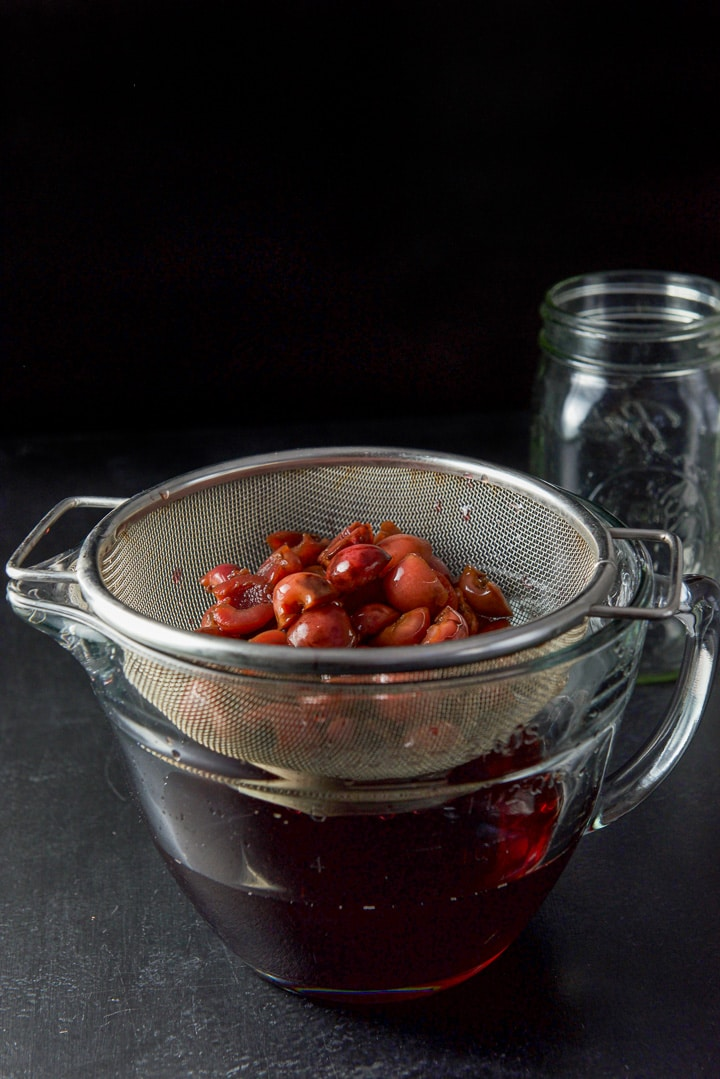 Cherries in a sieve over a bowl of the infused bourbon